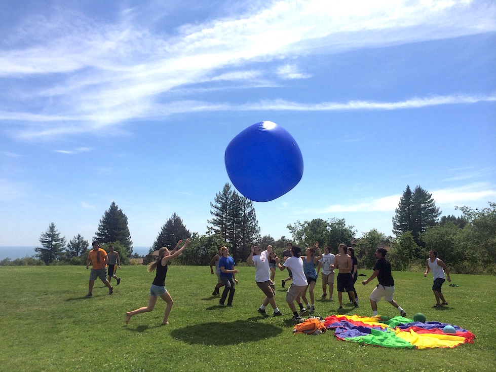 Students playing in a field with a large blue ball