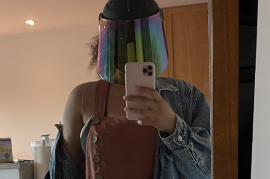 A brown-skinned person wearing a holographic faceshield while taking a mirror selfie.