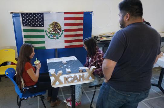 "Juan Morales-Rocha observes students playing his game ""Xicanx"""